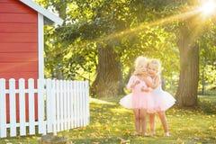 As duas meninas no campo de jogos contra o parque ou a floresta verde Imagem de Stock Royalty Free