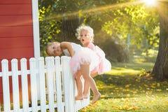 As duas meninas no campo de jogos contra o parque ou a floresta verde Imagens de Stock