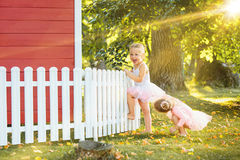 As duas meninas no campo de jogos contra o parque ou a floresta verde Fotos de Stock Royalty Free