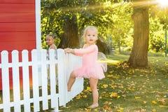 As duas meninas no campo de jogos contra o parque ou a floresta verde Fotografia de Stock Royalty Free
