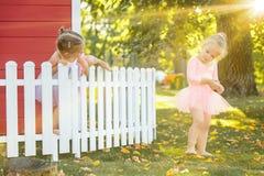 As duas meninas no campo de jogos contra o parque ou a floresta verde Imagem de Stock