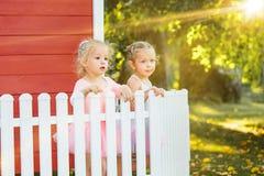 As duas meninas no campo de jogos contra o parque ou a floresta verde Imagens de Stock Royalty Free