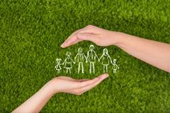 As duas mãos abertas da mulher que fazem uma família de proteção gesticulam Imagem de Stock