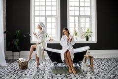 As duas mulheres novas bonitos vestidas nos vestidos e nas toalhas brancos de pingamento na cabe?a t?m o divertimento no banheiro fotos de stock