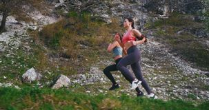 As duas senhoras bonitas têm um dia duro do exercício que corre no meio do sportswear vestindo de surpresa da estrada da montanha filme