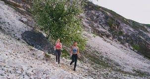 As duas senhoras carismáticas de sorriso têm um exercício duro na natureza através da estrada das pedras no meio de Mountain View filme