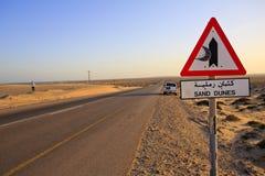 Sinal das dunas de areia com estrada e 4x4 Imagem de Stock