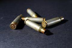 As embalagens vazias do shell da bala, em um fundo preto, fumam imagens de stock