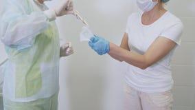 As enfermeiras abrem o pacote com as luvas est?reis para o doutor antes da cirurgia no hospital video estoque