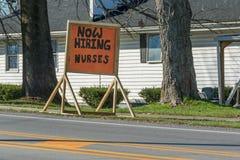 As enfermeiras agora de aluguer nutrem o sinal na frente de um lar de idosos local Imagem de Stock