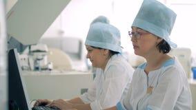As enfermeiras trabalham em um laboratório, usando computadores e o outro equipamento médico HD vídeos de arquivo