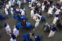 As enfermeiras vestiram peregrinos cristãos de seguimento e de ajuda em Lourd Imagem de Stock Royalty Free