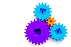 As engrenagens coloridas para a equipe ideal funcionam o modelo branco da opinião superior do fundo da tabela da tecnologia imagens de stock