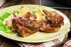 As entrecostos de porco da carne de porco serviram com batatas e molho triturados foto de stock
