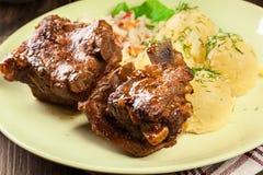As entrecostos de porco da carne de porco serviram com batatas e molho triturados foto de stock royalty free