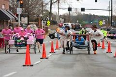 As equipes abaixam a rua parva das camas na raça do Fundraiser imagem de stock