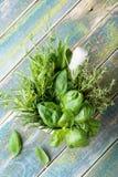 As ervas aromáticas no almofariz rolam na opinião de tampo da mesa de madeira rústica Manjericão, tomilho, alecrins e estragão In foto de stock royalty free