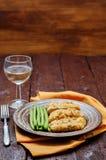 As ervas do queijo dos pães ralados cozeram o bacalhau com feijões verdes Fotos de Stock