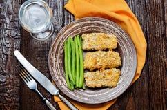 As ervas do queijo dos pães ralados cozeram o bacalhau com feijões verdes Foto de Stock