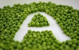 as ervilhas verdes arranjaram em uma ordem para fazer o alfabeto A no fundo branco imagens de stock royalty free