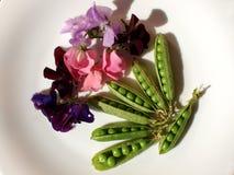 As ervilhas verdes em um fundo branco, com flores decoraram Foto de Stock