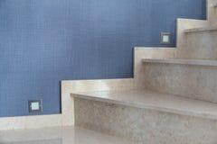 As escadas de mármore internas com fundo azul do papel de parede e as escadas iluminam-se imagem de stock