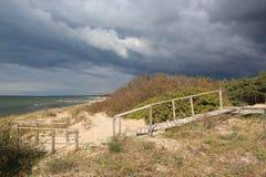 As escadas de madeira nas dunas e na areia de Forest Near The Baltic Sea encalham/nuvens de tempestade assustadores assustadores imagens de stock royalty free
