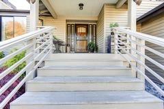 As escadas de madeira pintaram branco conduzem ao patamar coberto acolhedor da entrada Imagem de Stock