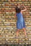 As escaladas da menina à parede foto de stock