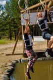As escaladas da menina em anéis sobre a água Raça dos heróis Fotos de Stock Royalty Free