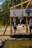 As escaladas da menina em anéis sobre a água Raça dos heróis Foto de Stock Royalty Free