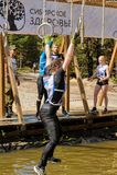 As escaladas da menina em anéis sobre a água Raça dos heróis Fotografia de Stock