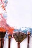As escovas da composição com coram ou sombra de tons cor-de-rosa, azuis e corais polvilhada no fundo branco Fotografia de Stock Royalty Free
