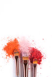 As escovas da composição com coram ou sombra de tons cor-de-rosa, vermelhos e corais polvilhada no fundo branco Foto de Stock