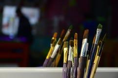 As escovas de pintura da arte no copo são ficadas situadas no children' s mante distraído fotos de stock