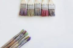 As escovas de pintura da cor na tabela branca Fotografia de Stock