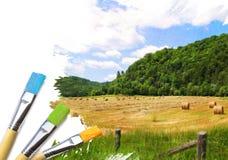 As escovas do artista com uma metade terminada pintaram a lona Fotografia de Stock Royalty Free