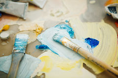 As escovas e a paleta de pintura da arte no fundo da pintura espirram Imagens de Stock