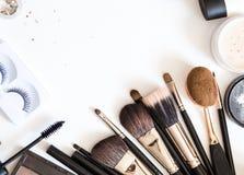 As escovas para cosméticos decorativos para compõem na opinião superior do fundo branco flatlay imagens de stock