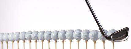 As esferas de golfe alinhadas e aprontam-se para bater Foto de Stock Royalty Free