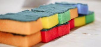 as esponjas Multi-coloridas para lavar e limpar alinharam em seguido imagens de stock