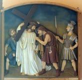 as 5as estações da cruz, Simon de Cyrene levam a cruz Fotografia de Stock Royalty Free