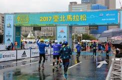 As estações de acabamento na maratona 2017 internacional de Taipei comemoram enquanto cruzam o meta Fotos de Stock