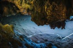 As estalactites iluminadas bonitas da pedra calcária em Adygeya cavam, rio subterrâneo com reflexão da luz azul Imagens de Stock Royalty Free