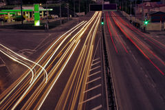 As estradas de cidade e o carro movente com borrão iluminam-se completamente imagem de stock