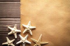 As estrelas do mar e o papel feito a mão cobrem na tabela de madeira Imagem de Stock