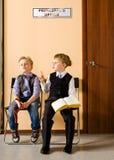 As estudantes estão sentando-se ao lado do escritório do principal fotos de stock royalty free