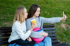 As estudantes pequenas estão sentando-se em um banco No verão no parque há 2 meninas acampar Em suas mãos guarda um vidro fotografia de stock royalty free