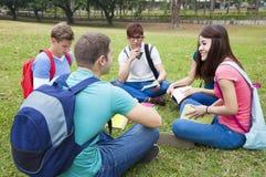 As estudantes universitário que estudam e discutem junto no terreno Fotografia de Stock Royalty Free