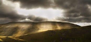 As explosões da luz solar iluminam acima a montanha Imagem de Stock Royalty Free